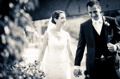 b&w wedding photo of bride and groom holding hands